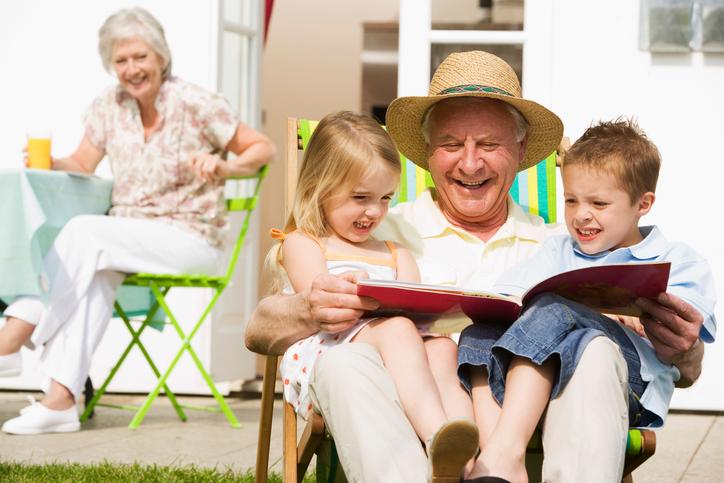 Grandfather reading to grandchildren
